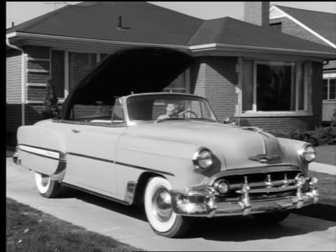 b/w 1953 woman putting top down on convertible sitting in driveway of suburban house - convertible top stock videos & royalty-free footage