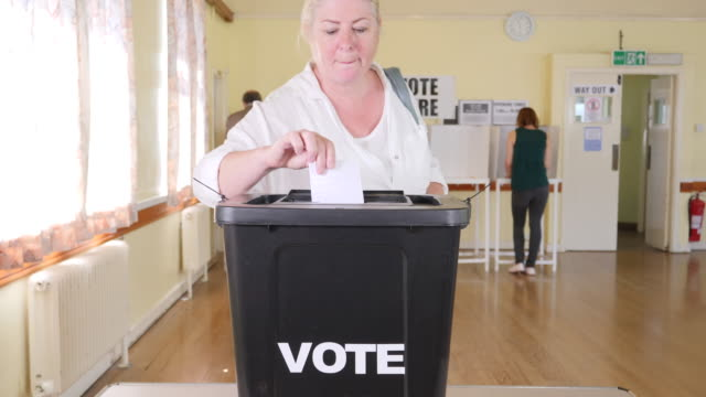 4k: woman putting vote in ballot box at the election - voting at polling station - voting booth stock videos and b-roll footage