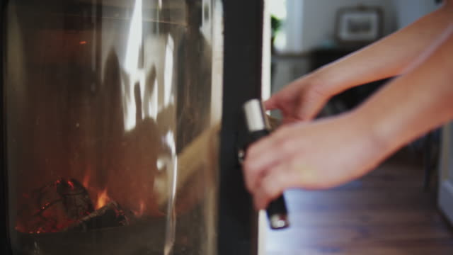 woman putting wood into a fire place. - kamin stock-videos und b-roll-filmmaterial