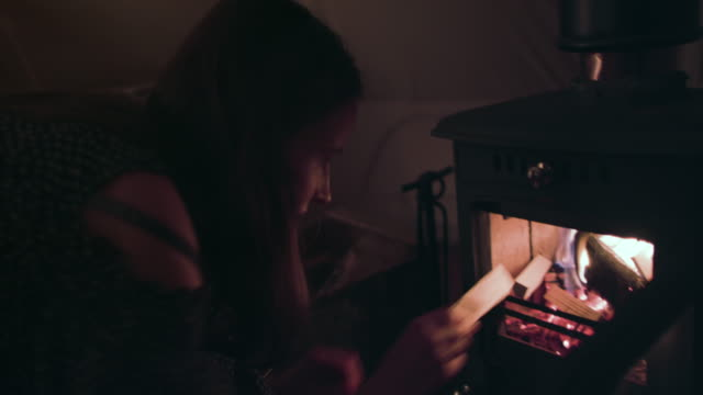 Woman putting wood into stove