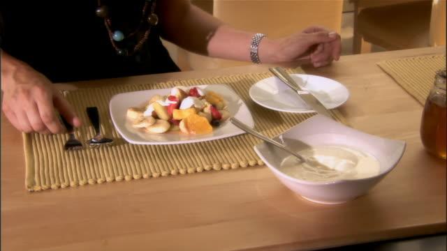 woman putting yogurt on fresh fruit at breakfast / eating fruit and talking - cibo biologico video stock e b–roll