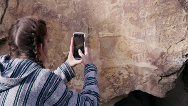 woman raising phone to take picture of petroglyphs - anasazi stock videos & royalty-free footage