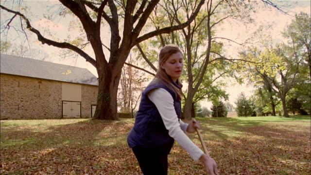 vídeos de stock e filmes b-roll de ms, woman raking leaves, usa, pennsylvania, solebury - ancinho equipamento de jardinagem