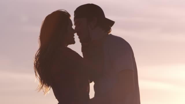 vidéos et rushes de woman reaches for mans face and pulls him in for a kiss - embrasser sur la bouche