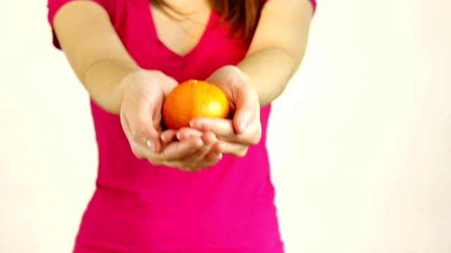 Woman reaches forward with orange in hands