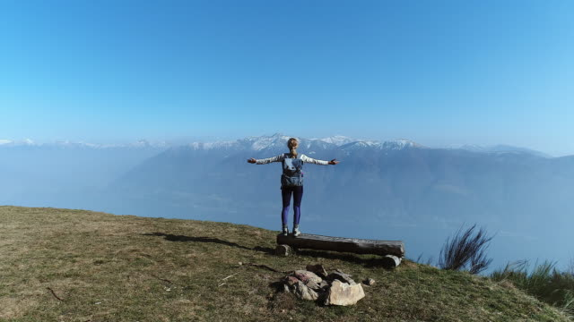 Woman reaches mountain top, arms outstretched