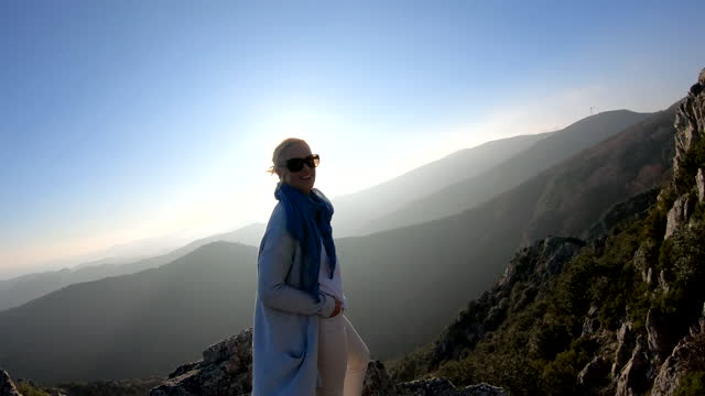 woman reaches summit of mountain overlook, enjoys view - incidental people stock videos & royalty-free footage