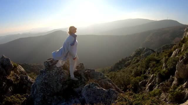 vídeos y material grabado en eventos de stock de woman reaches summit of mountain overlook, enjoys view - top