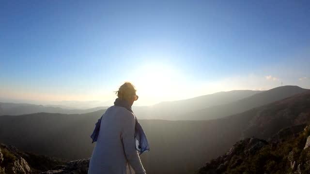 vidéos et rushes de woman reaches summit of mountain overlook, enjoys view - discovery