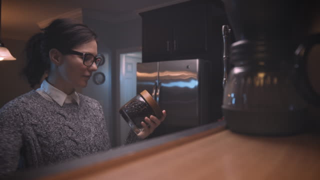 vídeos de stock e filmes b-roll de woman reaching for a jar of fresh roasted coffee beans from kitchen cabinet at home. - armário
