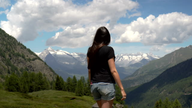 Woman reaching the mountain top on the Alps