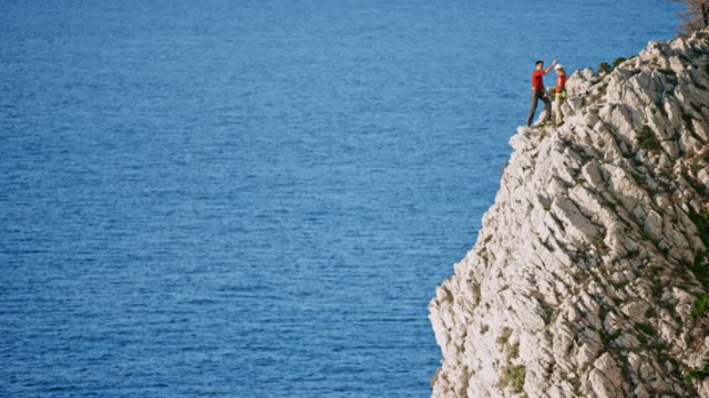 LD Woman reaching the top of the cliff above the sea where her male partner is waiting for her
