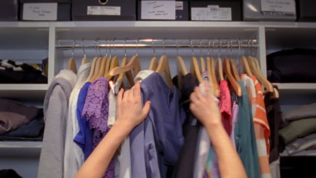 CU Woman reaching up to sort through rack of clothes in closet, New York City, New York, USA