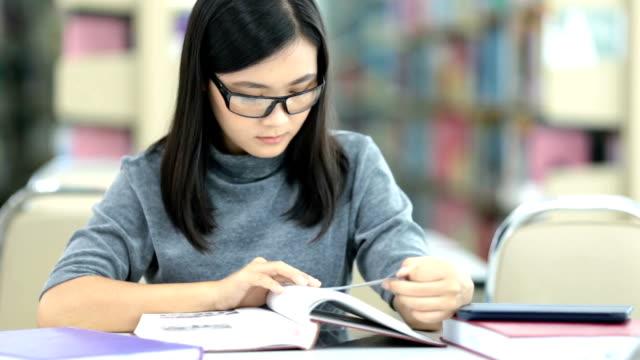 stockvideo's en b-roll-footage met vrouw lees een boek in de bibliotheek - leesbril