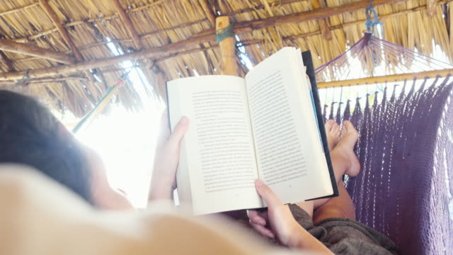 vídeos de stock e filmes b-roll de woman reading a book and swinging in a hammock. she is under a porch made by palm in a cabin at an idylic tropical location. - cama de rede