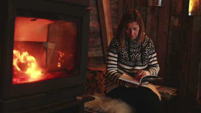 ws woman reading a book by the fireplace - cottage stock videos and b-roll footage