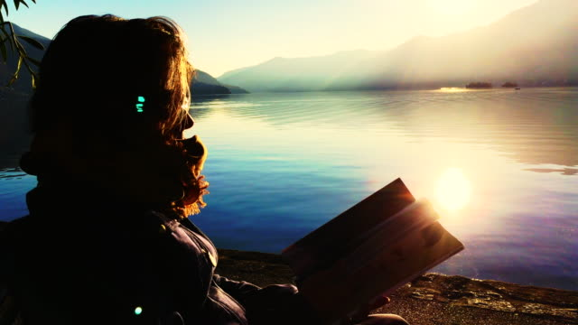 woman reading a book close to alpine lake with mountain and sunlight - in den vierzigern stock-videos und b-roll-filmmaterial