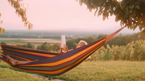 vidéos et rushes de femme de ds affichant un livre dans un hamac dans le vignoble - été