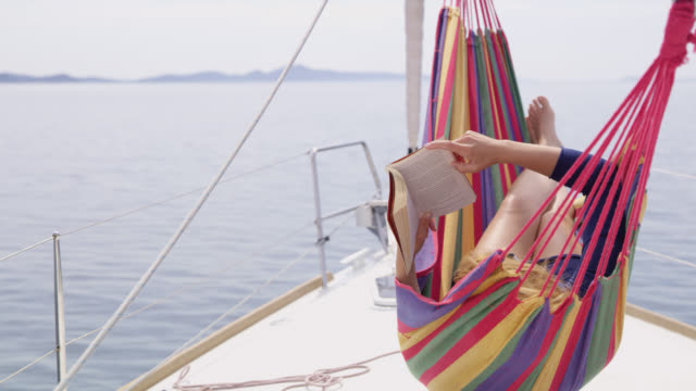 ds ms woman reading a book in a hammock on a sailboat - patio stock videos & royalty-free footage