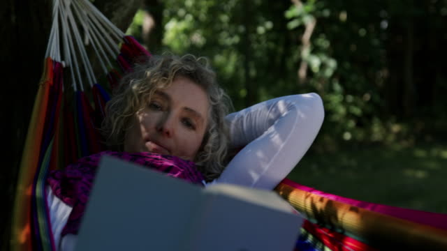 Woman reading a book in a hammock.