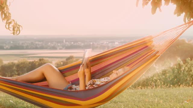 ds kvinna läser en bok i en hängmatta - hängmatta sol bildbanksvideor och videomaterial från bakom kulisserna