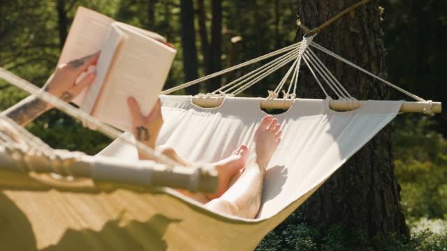 kvinna läser en bok i en hängmatta - hängmatta sol bildbanksvideor och videomaterial från bakom kulisserna