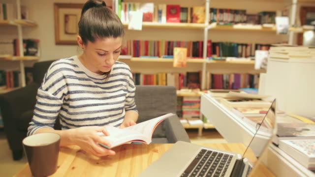 donna leggendo un libro nella libreria. - libro di testo video stock e b–roll