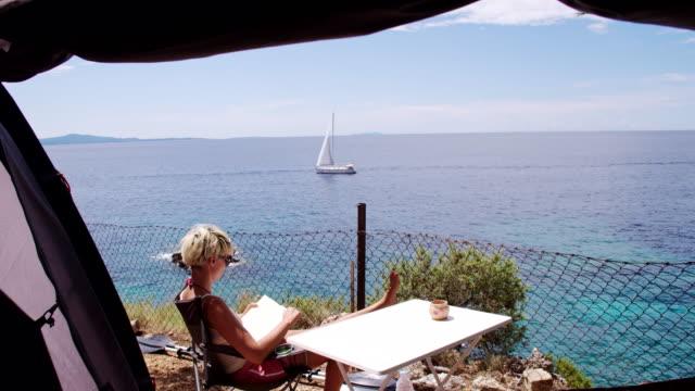 vídeos de stock, filmes e b-roll de ls ds mulher lendo um livro no camp - cadeira dobrável