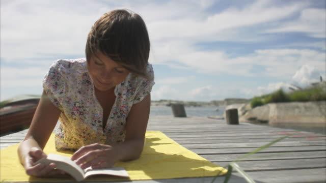 A woman reading a book on a jetty Huvudskar Stockholm archipelago Sweden.