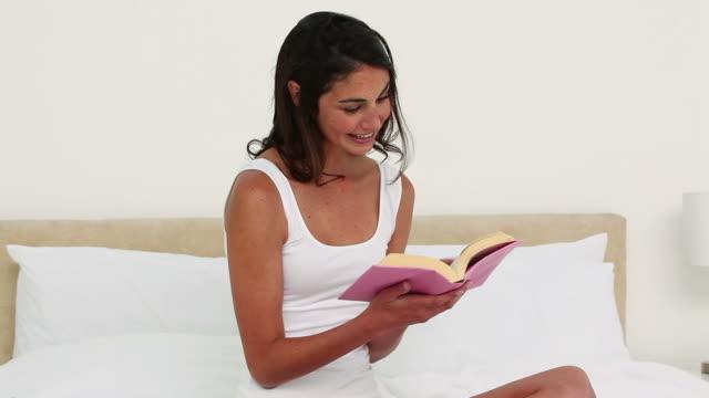 woman reading a book on her bed - korslagda ben bildbanksvideor och videomaterial från bakom kulisserna