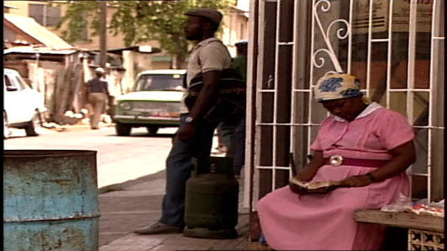 Woman Reading a Book on Stoop and Various People Walking By in Jamaica