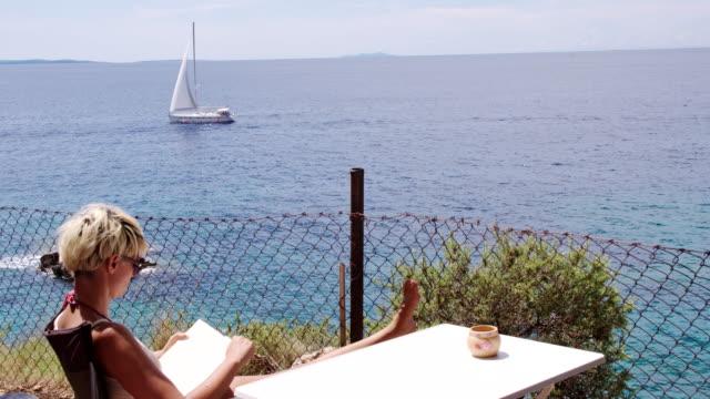 vídeos de stock, filmes e b-roll de ls mulher lendo um livro na praia - cadeira dobrável