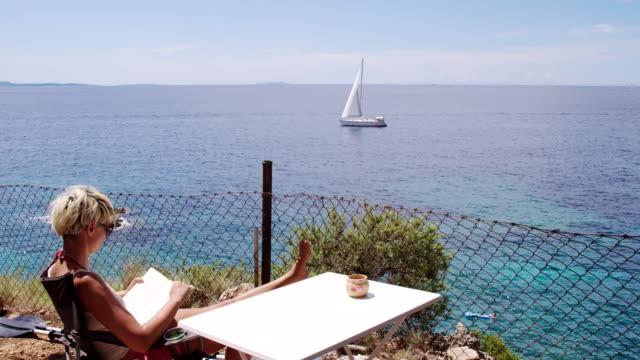 vídeos de stock, filmes e b-roll de ls ds mulher lendo um livro na praia - cadeira dobrável