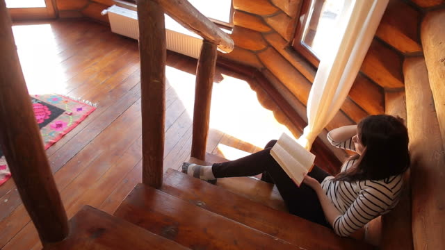 Woman reading a book on the cabin stairs.