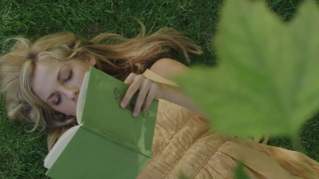 woman reading a book on the grass