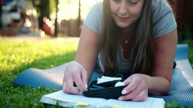 woman reading a book outdoors and checking blood glucose level - type 1 diabetes stock videos & royalty-free footage