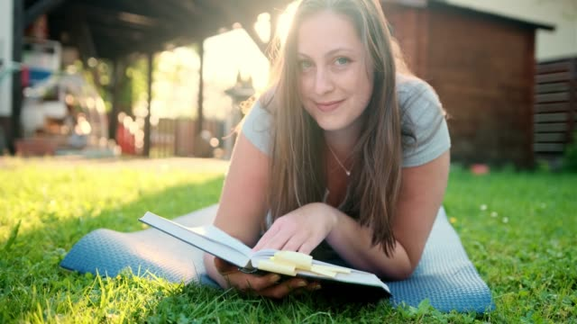 woman reading a book outdoors and looking at camera - type 1 diabetes stock videos & royalty-free footage
