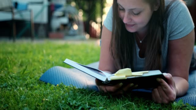 woman reading a book outdoors and lying in the grass - type 1 diabetes stock videos & royalty-free footage