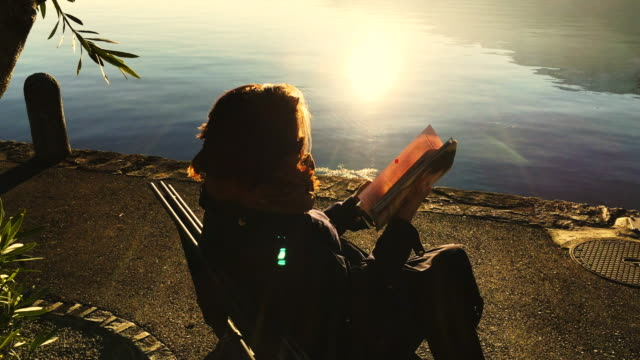 woman reading a magazine close to alpine lake with mountain and sunlight - in den vierzigern stock-videos und b-roll-filmmaterial