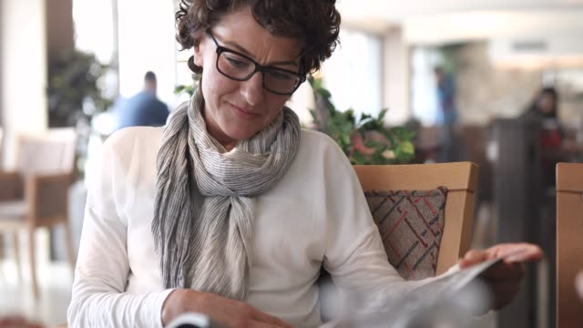 woman reading a magazine in a restaurant - 40 44 anni video stock e b–roll