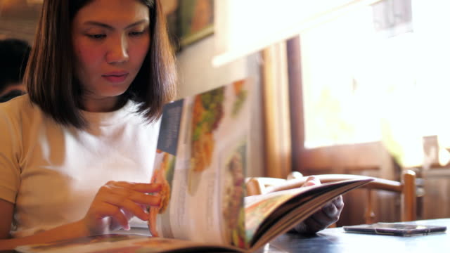 woman reading a menu at restaurant , slow motion - menu stock videos & royalty-free footage