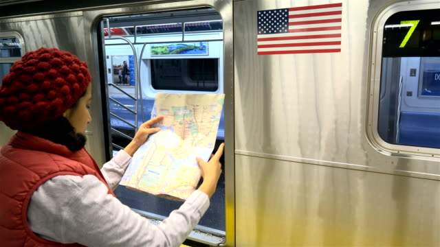 stockvideo's en b-roll-footage met woman reading a subway map, new york city - getal 7
