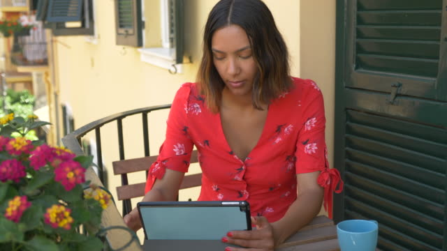 a woman reading a tablet mobile device e-reader traveling in a luxury resort town in italy, europe. - slow motion - electronic book stock videos & royalty-free footage