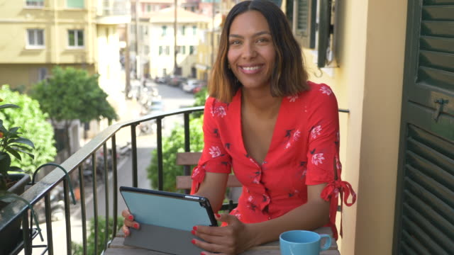 A woman reading a tablet mobile device e-reader traveling in a luxury resort town in Italy, Europe. - Slow Motion