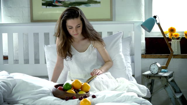 Woman reading and eating in bed