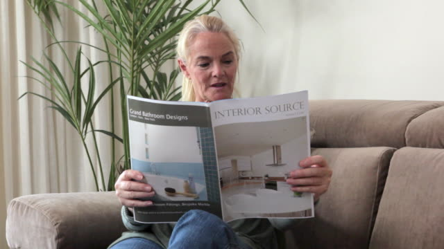 woman reading and getting inspiration from interior design magazine - 雑誌点の映像素材/bロール