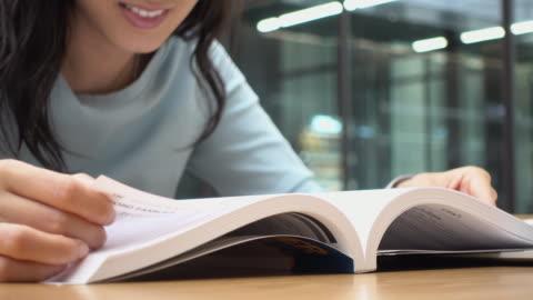 stockvideo's en b-roll-footage met vrouw lezen en open boek pagina - study