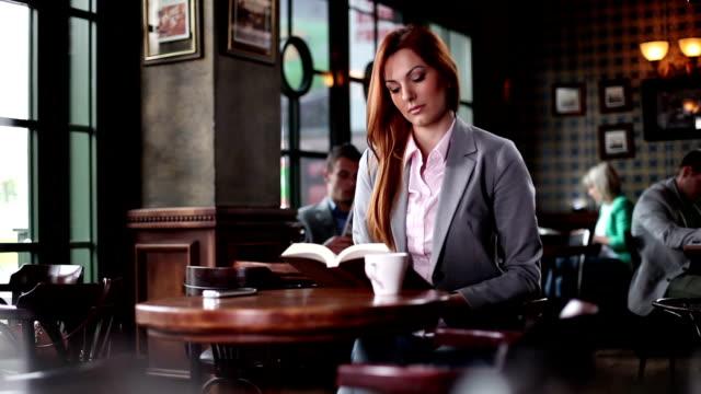Femme lisant sur un café