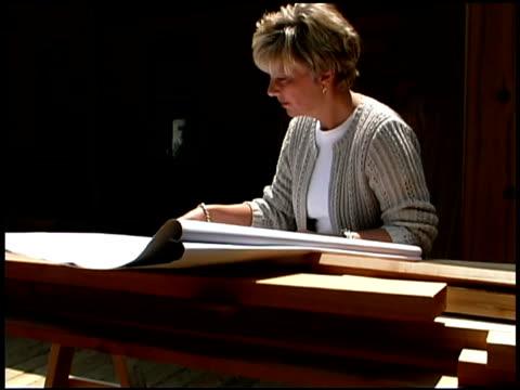 vidéos et rushes de woman reading blueprints - une seule femme d'âge moyen
