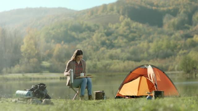本を読んでいて、湖のほとりにコーヒーの女性 - キャンプする点の映像素材/bロール